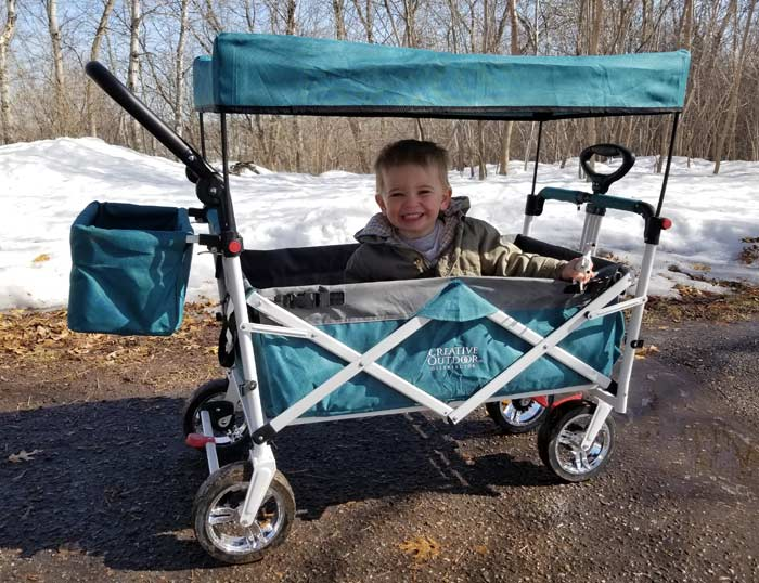 toddler riding push wagon stroller